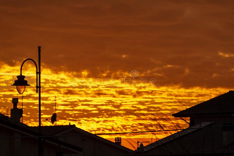 Beautiful golden sunset over the roofs of a Tuscan village with dramatic sky. Italy royalty free stock photography