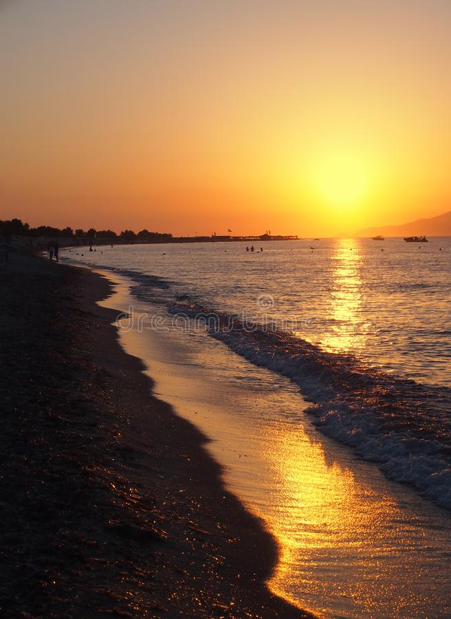 Beautiful golden sunset reflected on the sea and wet beach sand in Kos Greece stock photography