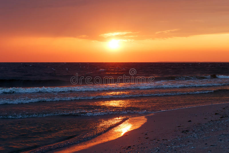 Beautiful golden sunset in the sea with saturated sky and clouds. Reflection in the water. Rocky coastal line. Peaceful serene lan royalty free stock photography