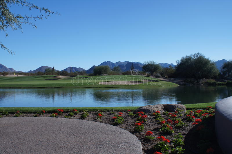 Beautiful Golf Course. Beautiful desert golf course with mountains and cactus in the background with a beautiful pond in the forground stock image