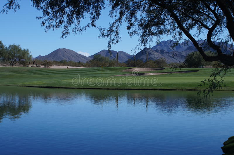 Beautiful Golf Course. Beautiful desert golf course with mountains and cactus in the background with a beautiful pond in the forground royalty free stock photography