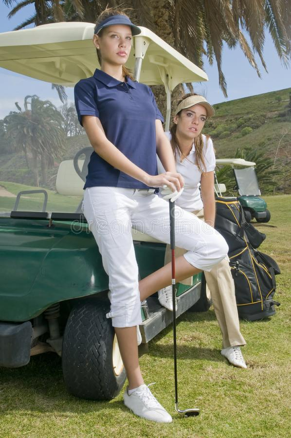 Beautiful golf players in their golf cars stock images