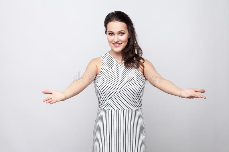 Beautiful good natured young brunette woman with makeup, striped dress standing, looking at camera with toothy smile, crossed arms royalty free stock images