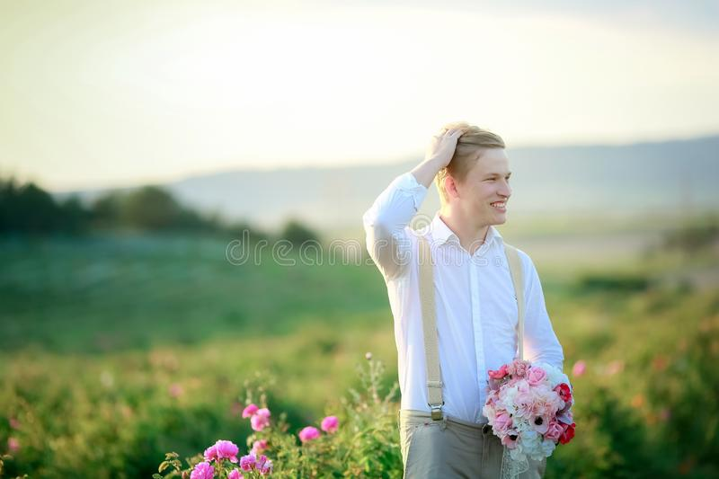 Beautiful gorgeous bride and stylish handsome groom, rustic couple in a rose field stock images