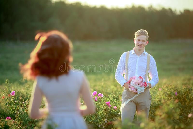 Beautiful gorgeous bride and stylish handsome groom, rustic couple in a rose field stock photos