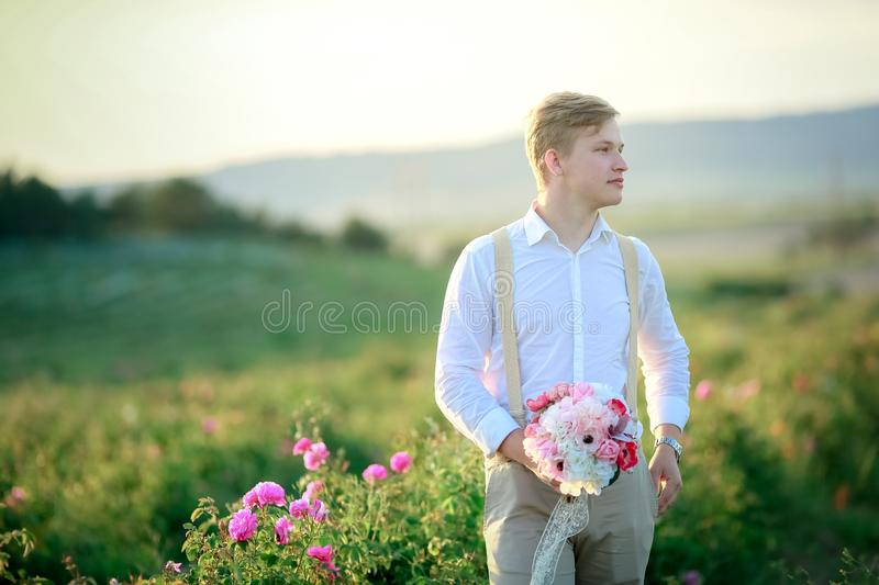 Beautiful gorgeous bride and stylish handsome groom, rustic couple in a rose field royalty free stock image