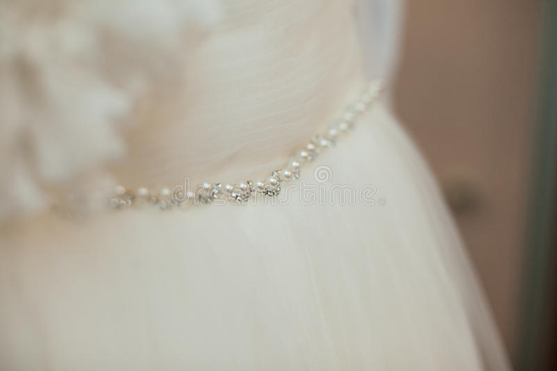 Beautiful gorgeous flower and pearl belt on fabulous wedding dress.  stock photos