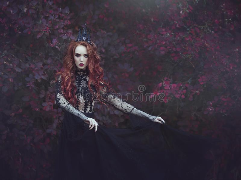 A beautiful gothic princess with pale skin and long red hair wearing a crown and a black dress against the backdrop of burgundy le. Aves. The costume of the dark royalty free stock photo