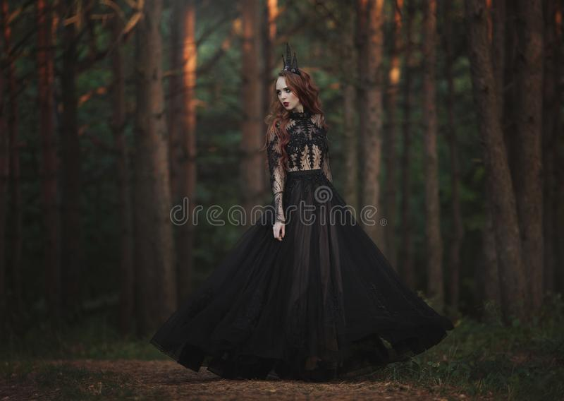A beautiful gothic princess with pale skin and very long red hair in a black crown and a black long dress in a misty fairy forest. The costume of the dark stock photography