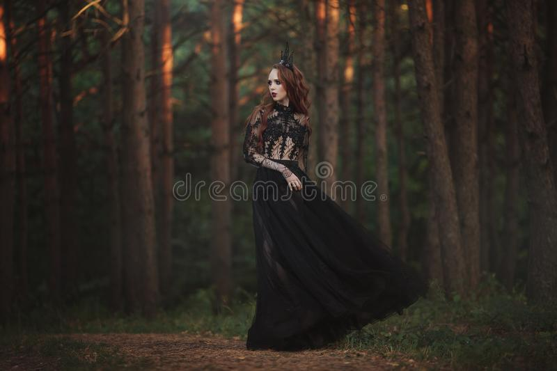 A beautiful gothic princess with pale skin and very long red hair in a black crown and a black long dress in a misty fairy forest. The costume of the dark royalty free stock image