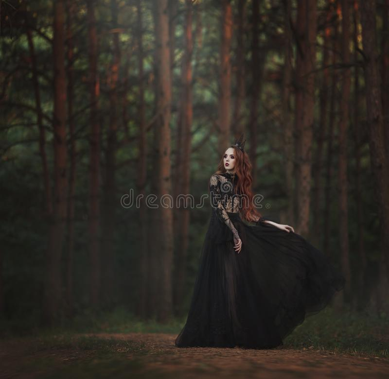 A beautiful gothic princess with pale skin and very long red hair in a black crown and a black long dress walks in a misty fairy-t stock photo