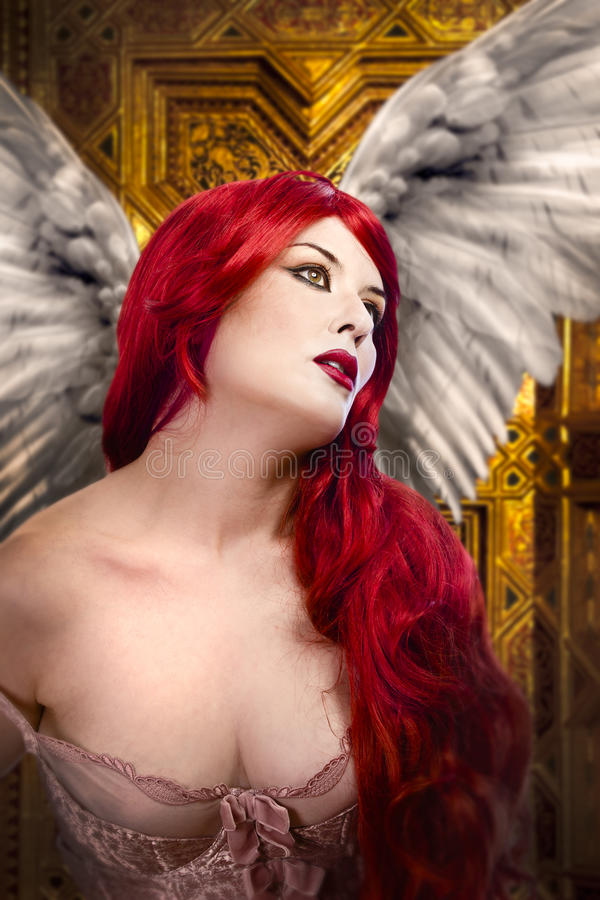 Beautiful gothic angel with wings. Red hair over gold background royalty free stock photos
