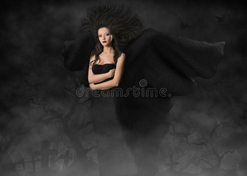 Beautiful gothic style woman with wings. Dark angel. Beautiful gothic style woman with wings standing in fog cemetery at black night stock photo