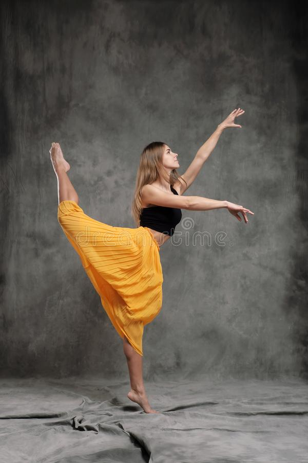 A beautiful graceful slender female dancer performs choreographic figures and movements on a gray dark fabric background royalty free stock images