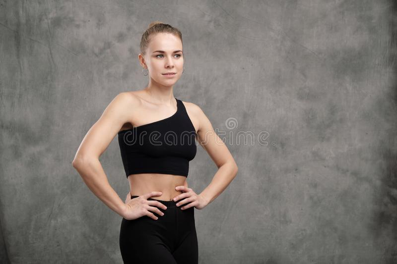 Beautiful graceful slender muscular woman dancer in black sportswear posing with her arms crossed on a gray dark fabric stock photo