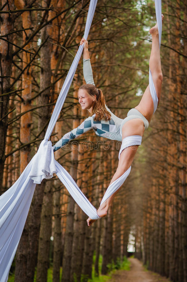 Beautiful and graceful trapeze artist performs exercises on aerial silk. In the forest royalty free stock photos