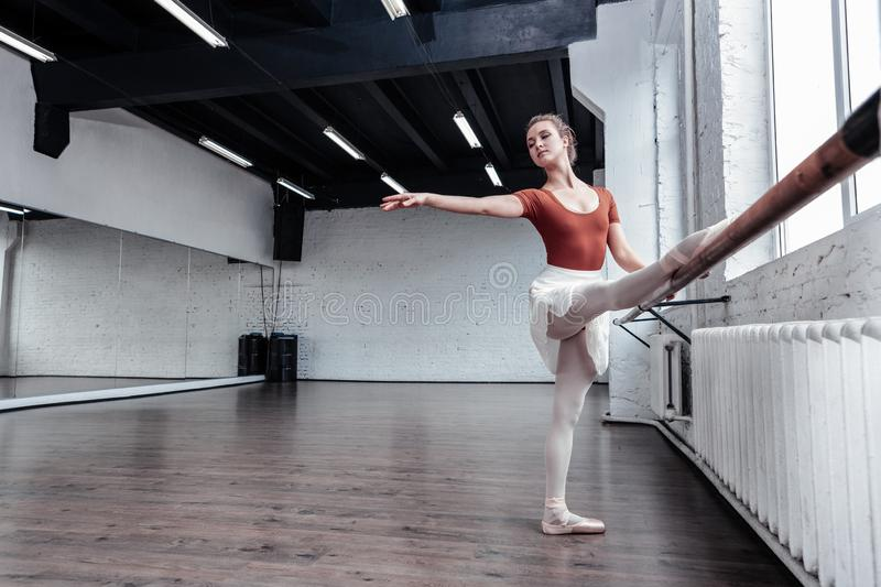 Beautiful graceful woman practicing her dancing movements. Special dance. Beautiful graceful woman standing in the hall while practicing the dancing movements stock images