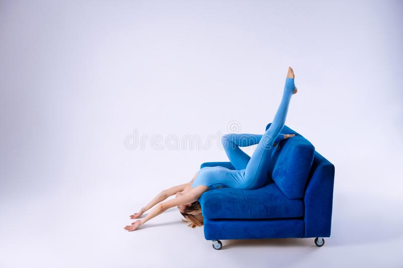Beautiful gracious woman lying upside down on the sofa royalty free stock images