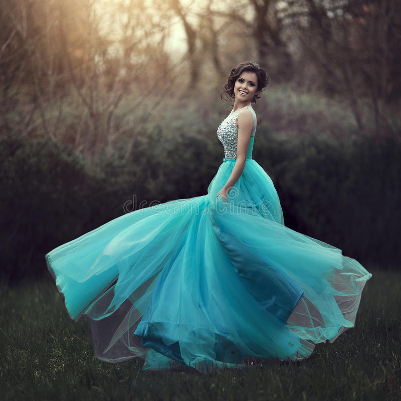 A beautiful graduate girl is spinning in a blue dress. Elegant young woman in a beautiful dress in the park. Art photo. stock photo