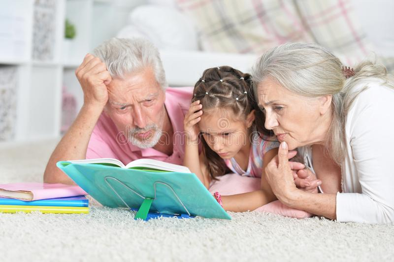 Portrait of grandparents reading book with little granddaughter. Beautiful grandparents reading book with little granddaughter at home royalty free stock images