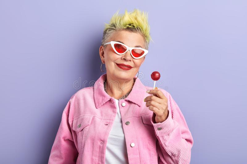 Beautiful granny holding candy with friut flavor. Closeup portrait, studio shot royalty free stock photos