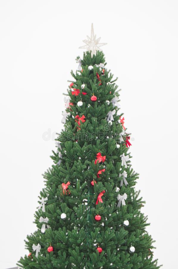 Beautiful green artificial Christmas tree decorated with shiny ribbons and balls isolated on white background, vertical shot. Spruce, pine, ornament, snapshot royalty free stock images