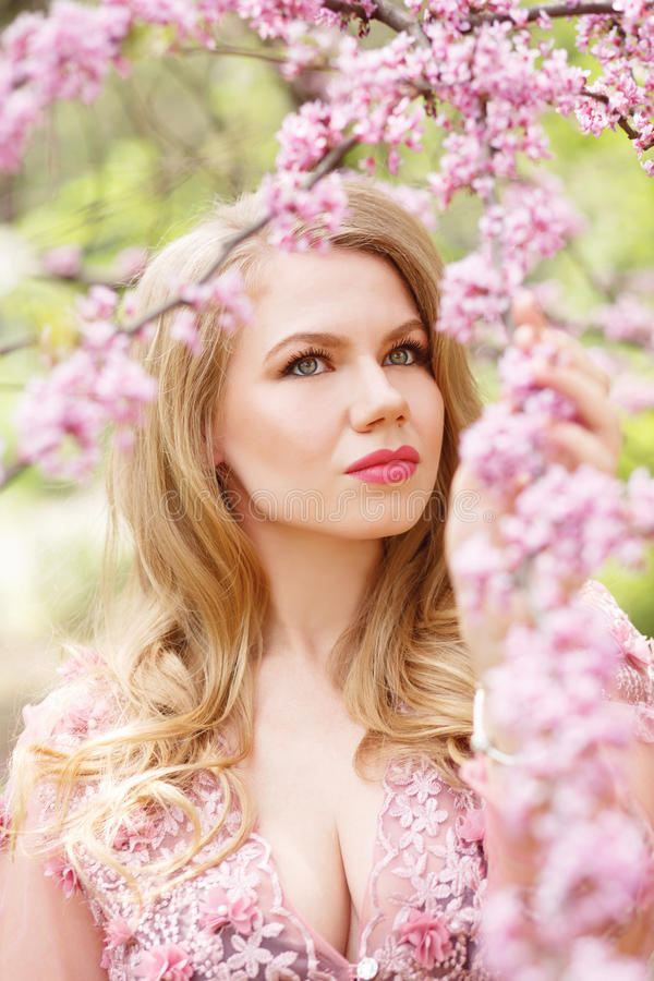 Beautiful green-eyed woman holding a cherry blossoming branch in hands. stock images