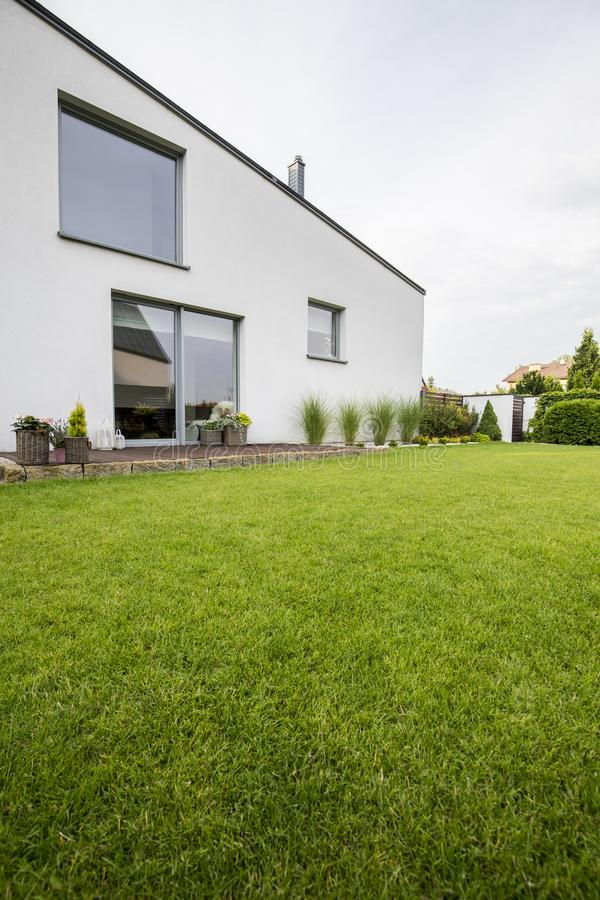 Beautiful green lawn in the backyard of a modern residential house with plants on a wooden terrace and big windows stock image