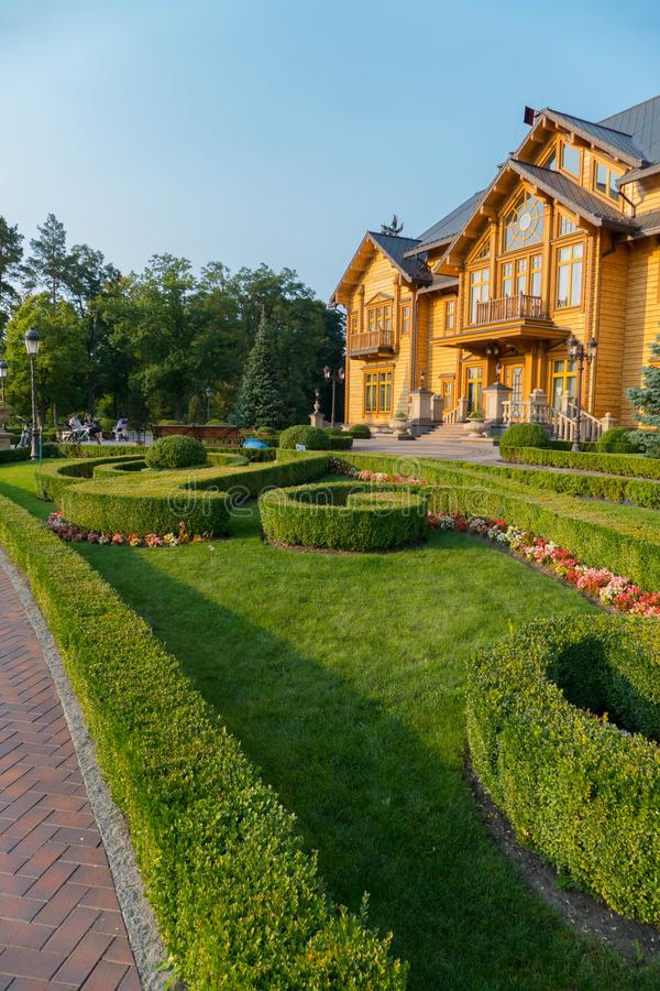Beautiful green lawn framed by bushes and flowers in front of a large rich mansion, the residence of Yanukovych Museum. Of Corruption of Ukraine Mezhyhirya royalty free stock photos
