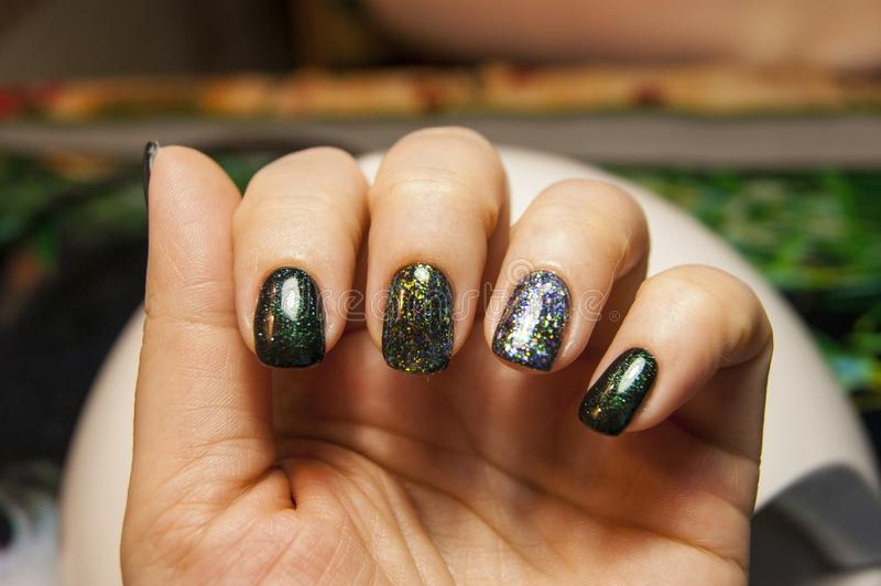 Beautiful green manicure, nail polish on nails of different shades of green, with a slight sheen and large shimmer. Womeтs hands - beautiful green manicure royalty free stock photography