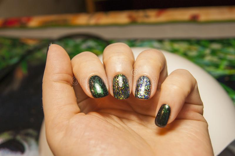 Beautiful green manicure, nail polish on nails of different shades of green, with a slight sheen and large shimmer. Womens hands - beautiful green manicure, nail royalty free stock photo