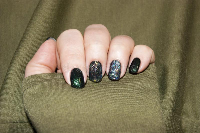 Beautiful green manicure, nail polish on nails of different shades of green, with a slight sheen and large shimmer. Womens hands - beautiful green manicure, nail stock photography