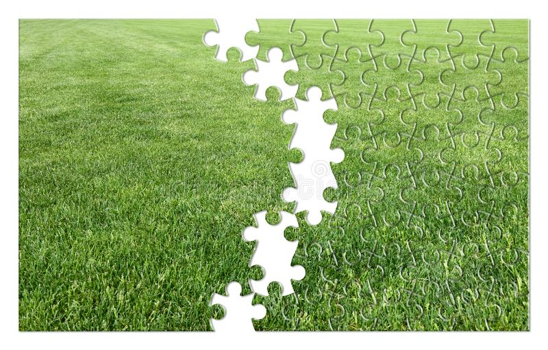 Beautiful green mowed lawn in jigsaw puzzle shape - concept image royalty free stock photography