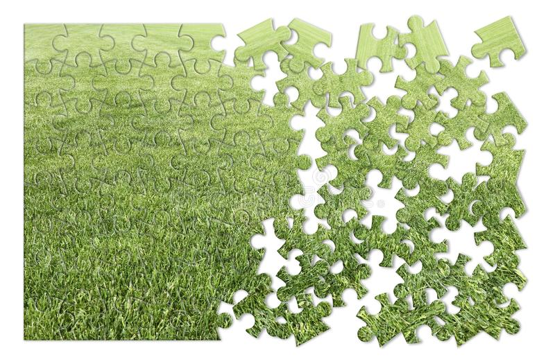 Beautiful green mowed lawn in puzzle shape on white background royalty free stock photo