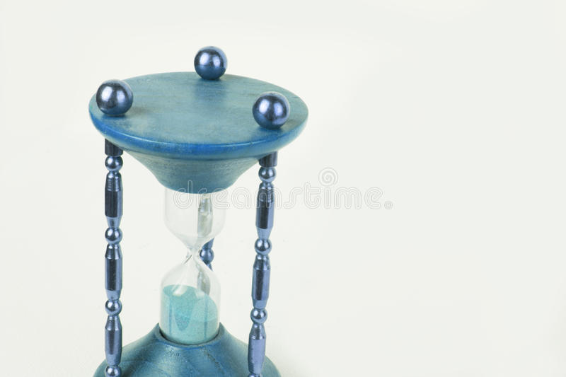 Beautiful green old timeglass / hour glass on white studio background. Old wooden hour / time glass with sand on white studio background, green, blue , turquoise royalty free stock images