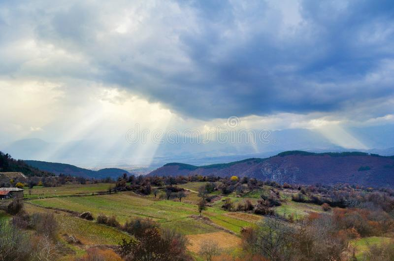 Beautiful Green Spring Meadows and Cloudy Sky with Sunny Rays. Beautiful landscape with green meadows and cloudy sky royalty free stock photography