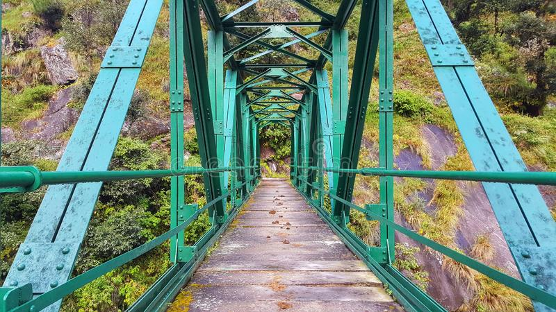 A beautiful green steel bridge over Madamaheswar ganga in the trek route n Uttarakhand. A Steel green bridge over Madamaheshwar Ganga in the Uttarakhand s most stock photos