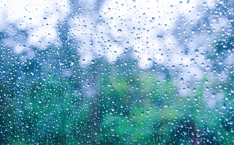 Beautiful greentree background in the rain. The beautiful greentree background with the beautiful waterdrops behind the window on the rainy day in the rainy royalty free stock photography