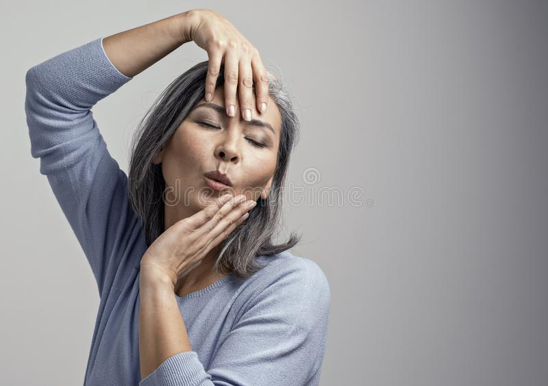 Attractive Asian woman is emotionally posing touching her head with hands royalty free stock photo
