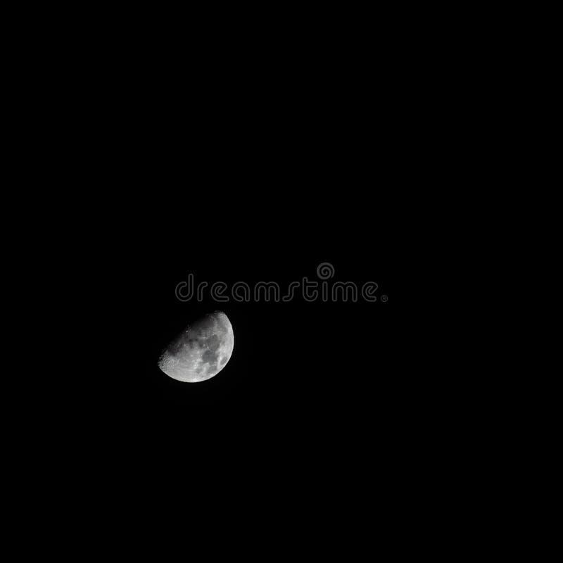 Beautiful grey half moon in the pitch black dark sky stock photos