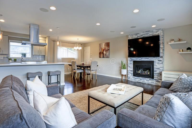 Beautiful grey living room with stone fireplace. Beautiful living room with stone fireplace. Open floor plan features kitchen and dining space royalty free stock photo