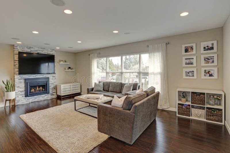 Beautiful grey living room with stone fireplace. Beautiful living room with stone fireplace and polished hardwood floor royalty free stock image