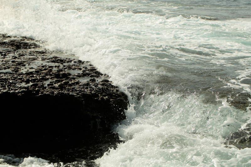 Beautiful grey sea stormy waves splash against black stony shore royalty free stock photography