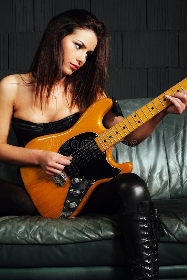 Beautiful guitarist sitting on couch stock images