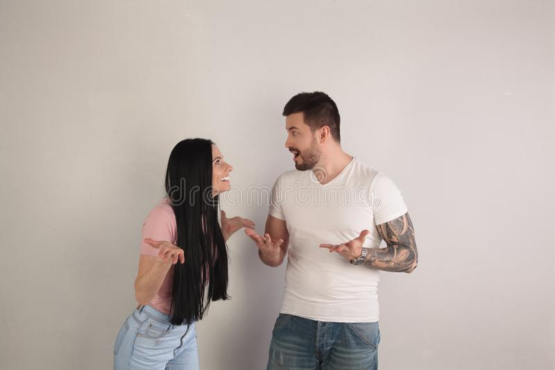 Beautiful guy and girl are looking surprised at each other, they do not understand what`s going on around. they stand in front of. The white background royalty free stock photo