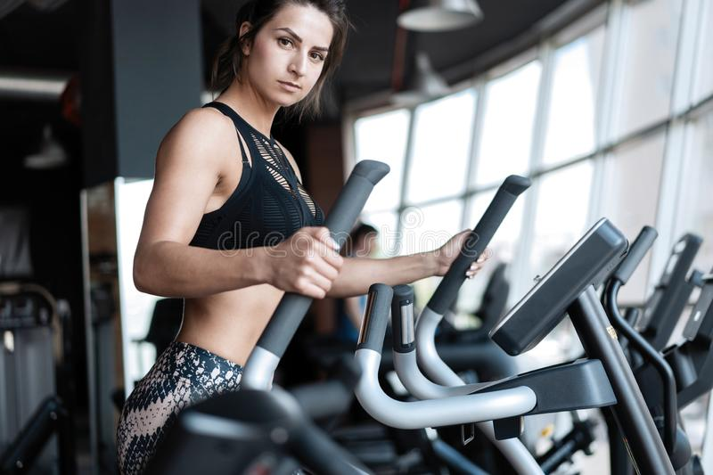 Beautiful gym woman exercising on a cardio machine smiling. royalty free stock photography