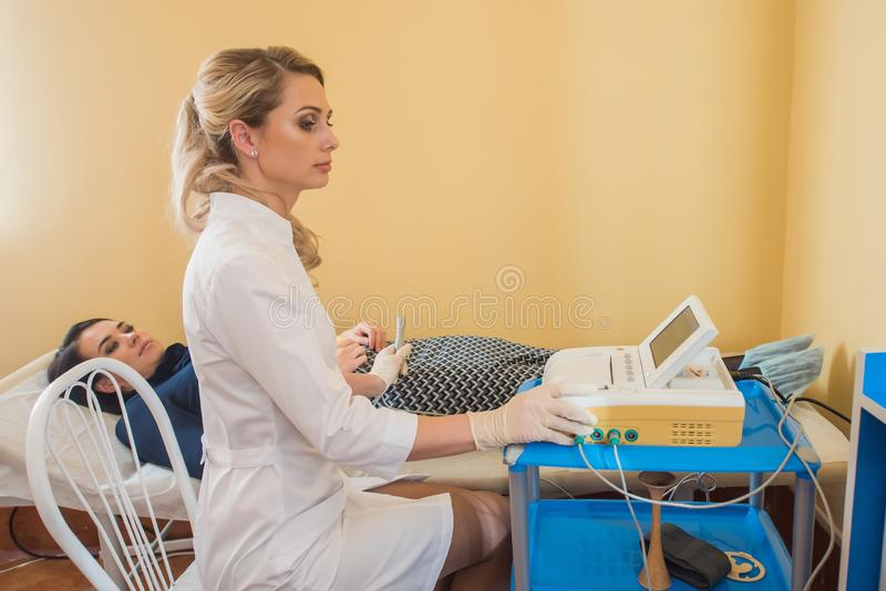 Beautiful gynecologist does cardiotocography of the fetus. A young doctor examines a patien. Checkup. royalty free stock photo
