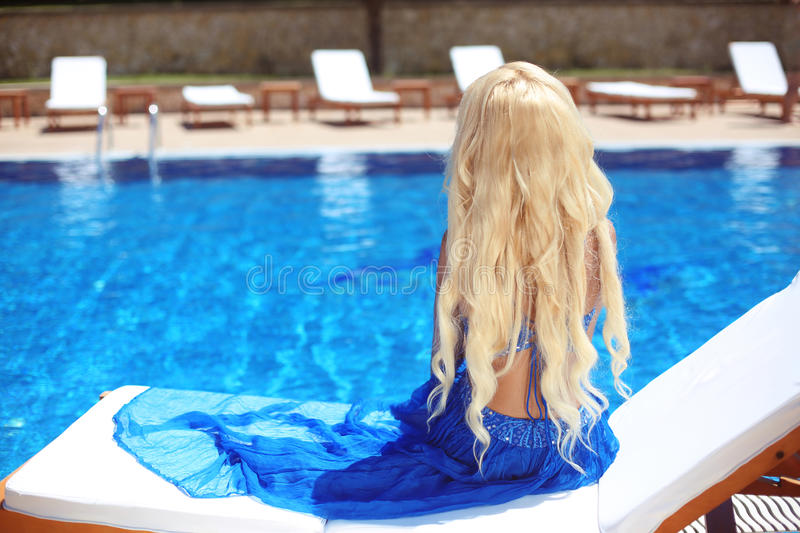 Beautiful Hair. Beauty blond woman with luxurious long hair sitting on beach bed, looking at swimming pool. stock photography