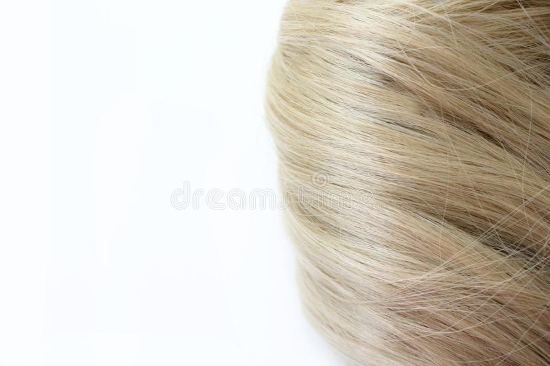 Beautiful hair. Light brown hair. Hair is gathered in a bun on a white background. With free space for text. For a poster or busin royalty free stock photography