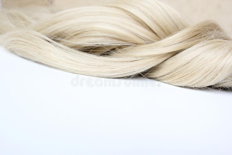 Beautiful hair. Light hair. Curl. Strand of hair. Curl on white background. With free space for text. For a poster or business car stock image